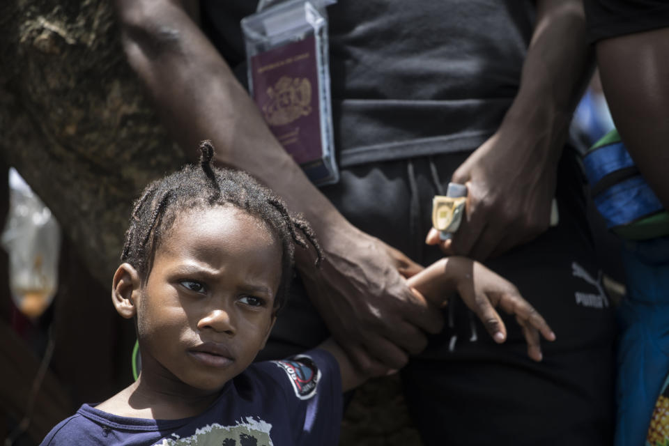 A migrant father hold his son´s hand as he waits to buy tickets for transportation by sea to Capurgana, on the border with Panama, from Necocli, Colombia, Thursday, July 29, 2021. Migrants have been gathering in Necocli as they move north towards Panama on their way to the U.S. border. (AP Photo/Ivan Valencia)