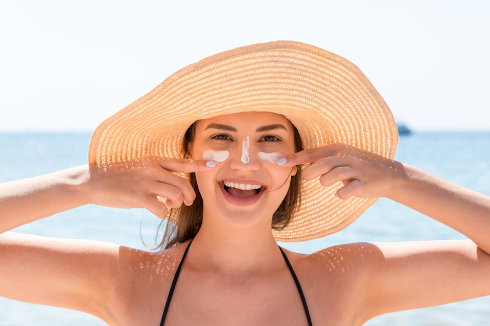 Beautiful young woman in hat is applying sunblock under her eyes and on her nose like Indian. Sun protection concept.
