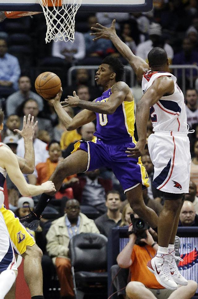 Los Angeles Lakers forward Nick Young (0) scores against Atlanta Hawks' Al Horford in the first half of an NBA basketball game, Monday, Dec. 16, 2013, in Atlanta. (AP Photo/John Bazemore)