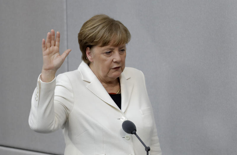 German Chancellor Angela Merkel takes the oath of office after she was elected for a fourth term as chancellor in the German parliament Bundestag in Berlin, Germany, Wednesday, March 14, 2018. (AP Photo/Michael Sohn)