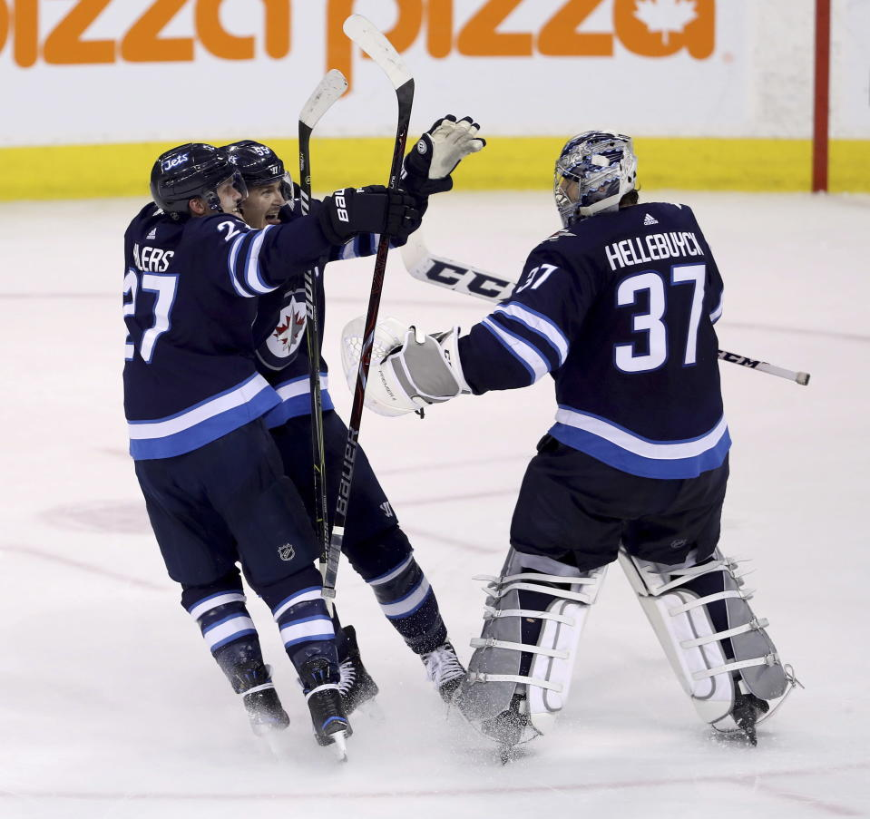 Winnipeg Jets' Nikolaj Ehlers (27) and Mark Scheifele (55) rush to goaltender Connor Hellebuyck (37) after he made the game-winning save against the Nashville Predators during the shootout following NHL hockey action in Winnipeg, Manitoba, Sunday, March 25, 2018. (Trevor Hagan/The Canadian Press via AP)