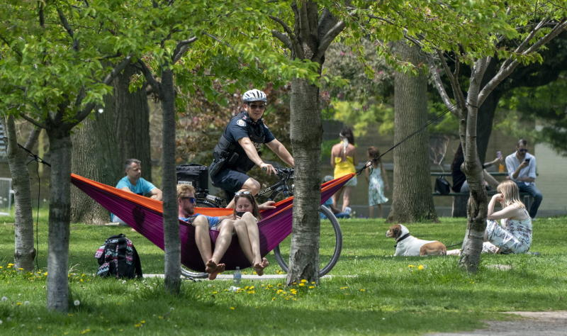 A bicycle police officer patrols Trinity Bellwoods Park in Toronto on Sunday, May 24, 2020. Warm weather and a reduction in COVID-19 restrictions have many looking to the outdoors for relief. (Frank Gunn/The Canadian Press via AP)