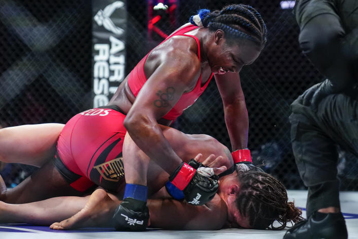 Claressa Shields, top, punches Brittney Elkin during a Professional Fighters League mixed martial arts bout in Atlantic City, N.J., early Friday, June 11, 2021. (AP Photo/Matt Rourke)