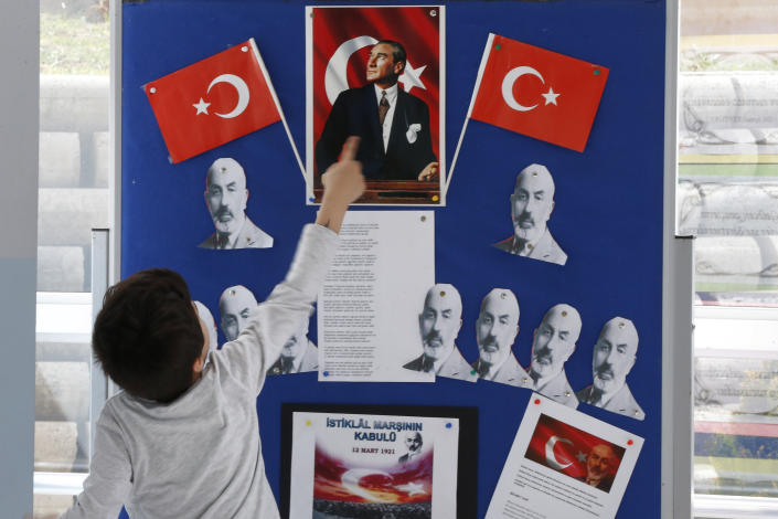 A boy shows the Turkish Republic founder Mustafa Kemal Ataturk portrait on a board school at a polling station during the local elections, in Istanbul, Sunday, March 31, 2019. Turkish citizens have begun casting votes in municipal elections for mayors, local assembly representatives and neighbourhood or village administrators that are seen as a barometer of Erdogan's popularity amid a sharp economic downturn.(AP Photo/Lefteris Pitarakis)