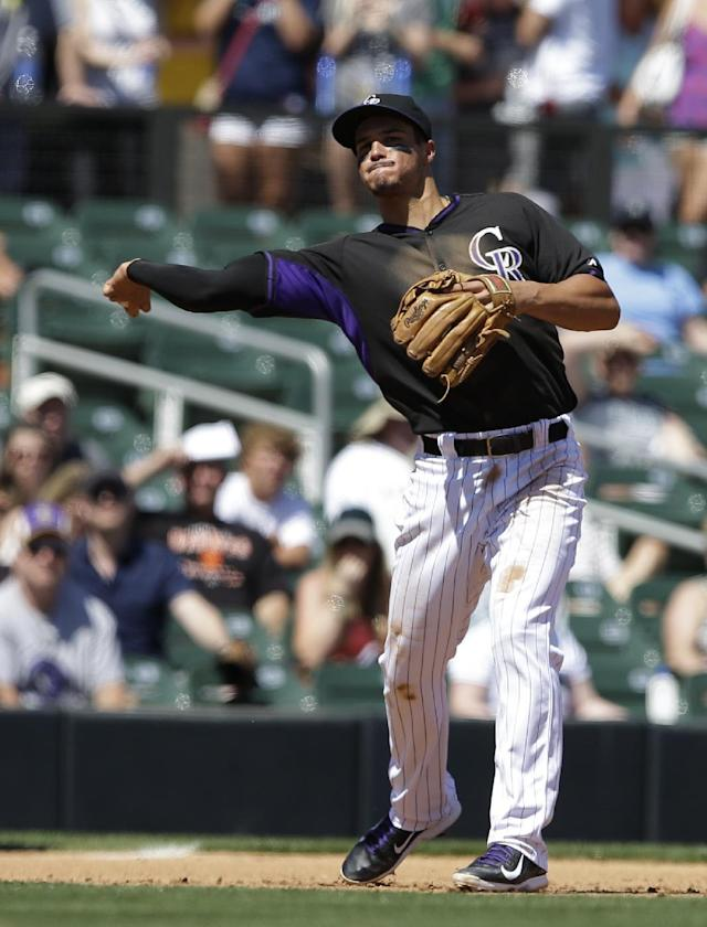 Colorado Rockies third baseman Nolan Arenado throws out Seattle Mariners' Abraham Almonte at first during the fourth inning of an exhibition baseball game Saturday, March 29, 2014, in Scottsdale, Ariz. (AP Photo/Darron Cummings)
