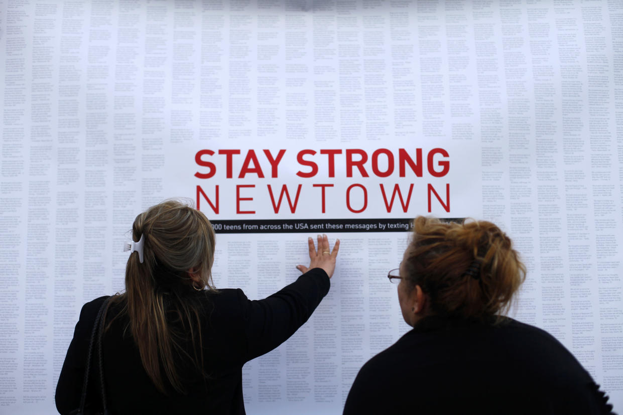 A woman touches a printout of messages of support and shared grief from teenagers around the United States at a memorial for the victims of the Sandy Hook Elementary School shooting in Newtown, Conn., Dec. 18, 2012. (Photo: Joshua Lott/Reuters)