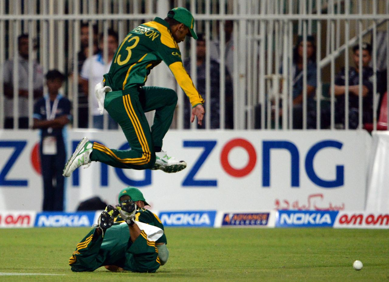 A South African cricketer jumps over a teammate that falls down during the five-match series against Pakistan in Sharjah Cricket Stadium in Sharjah on November 11, 2013. South Africa beat Pakistan by 117 runs in the fifth and final day-night international in Sharjah on Monday, clinching the five-match series 4-1.   AFP PHOTO/ASIF HASSAN        (Photo credit should read ASIF HASSAN/AFP/Getty Images)