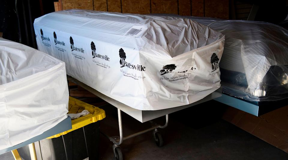 Covered empty caskets stand in a garage at Boyd Funeral Home on Jan. 14, 2021, in Los Angeles. (Photo: PATRICK T. FALLON via Getty Images)