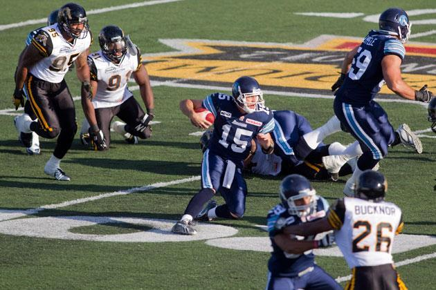 Toronto Argonauts quarterback Ricky Ray (centre, number 15) carries the ball forward against Hamilton Tiger-Cats during first half CFL pre-season action in Hamilton on Wednesday June 13 , 2013. THE CANADIAN PRESS/ Chris Young