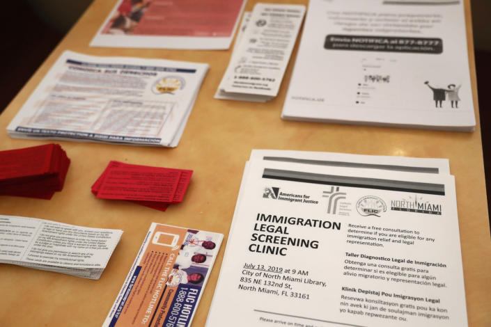 Flyers in English and Spanish are shown stacked at a nearby restaurant before immigration advocates gather them and hand them out, Thursday, July 11, 2019, in the Little Havana neighborhood in Miami. The Trump administration is moving forward with a nationwide immigration enforcement operation this weekend targeting migrant families. (AP Photo/Wilfredo Lee)
