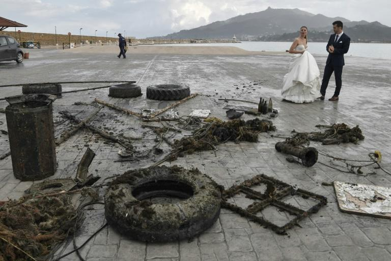 A newly-wed couple looks at the rubbish collected from the sea by volunteers from Aegean Rebreath (AFP Photo/LOUISA GOULIAMAKI)
