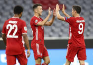Bayern's Ivan Perisic, centre, is congratulated by teammate Robert Lewandowski after scoring his team's second goal during the Champions League round of 16 second leg soccer match between Bayern Munich and Chelsea at Allianz Arena in Munich, Germany, Saturday, Aug. 8, 2020. (AP Photo/Matthias Schrader)