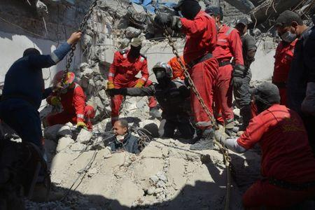 Iraqi firefighters look for bodies buried under the rubble, of civilians who were killed after an air strike against Islamic State triggered a massive explosion in Mosul