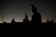 Members of the Afghan Special Forces keep a watch as others search houses in a village during a combat mission against Taliban, in Kandahar province