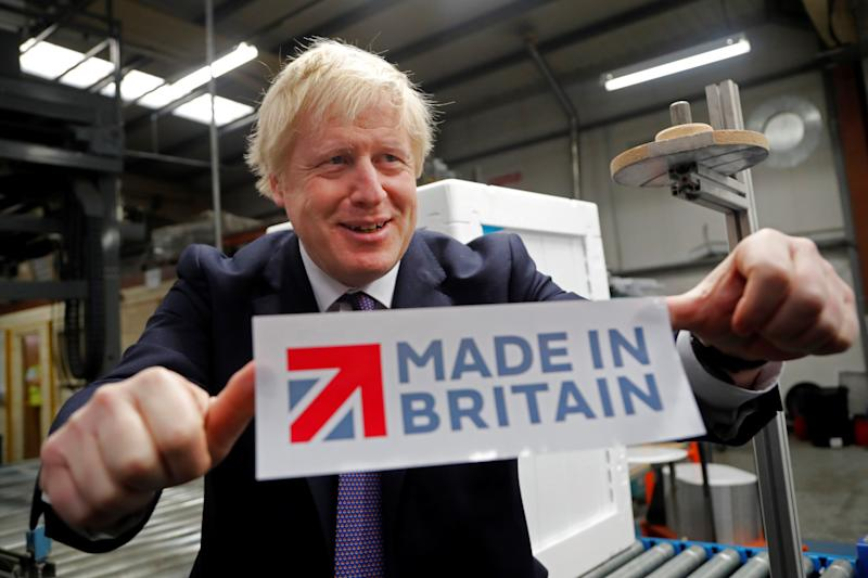 "Britain's Prime Minister Boris Johnson reacts as he poses with a ""made in Britain"" sticker during his general election campaign visit to Ebac, an electrical appliances manufacturer in Newton Aycliffe, north-east England on November 20, 2019. - Britain will go to the polls on December 12, 2019 to vote in a pre-Christmas general election. (Photo by Frank Augstein / POOL / AFP) (Photo by FRANK AUGSTEIN/POOL/AFP via Getty Images)"