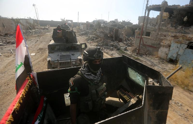 Members of Iraq's elite counter-terrorism service ride their military vehicles amidst destroyed buildings in Ramadi on December 29, 2015 (AFP Photo/Ahmad Al-Rubaye)