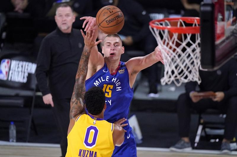 Los Angeles Lakers forward Kyle Kuzma (0) and Denver Nuggets center Nikola Jokic (15) compete for control of a rebound during the first half an NBA conference final playoff basketball game Friday, Sept. 18, 2020, in Lake Buena Vista, Fla. (AP Photo/Mark J. Terrill)