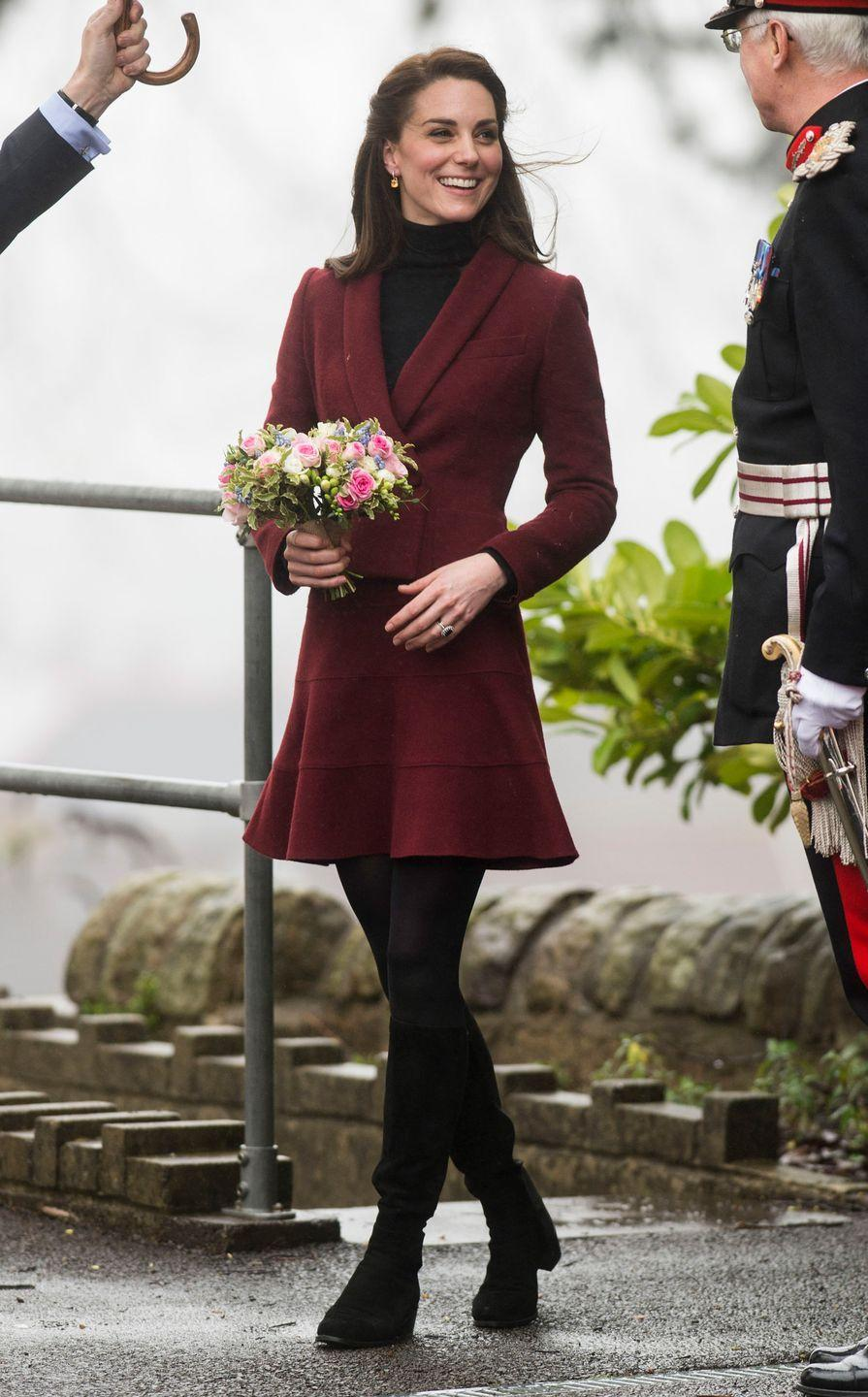 <p>The Duchess of Cambridge wears a burgundy Paule Ka skirt suit, black tights, and black knee-high <span>Stuart Weitzman</span> boots during a visit to Wales.</p>