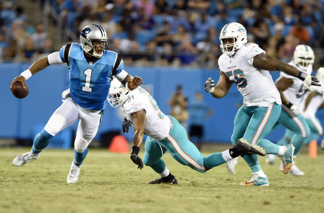 Carolina Panthers' Cam Newton (1) scrambles away from Miami Dolphins' Cameron Wake (91) and Davon Godchaux (56) in the first half of a preseason NFL football game in Charlotte, N.C., Friday, Aug. 17, 2018. (AP Photo/Mike McCarn)