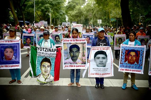 People hold posters of disappeared students during a protest in Mexico city, on September 26, 2015, to commemorate the first anniversary of Ayotzinapa school students disappearance (AFP Photo/Ronaldo Schemidt)