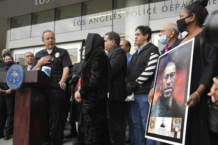 """FILE - In this June 5, 2020, file photo, Los Angeles police chief Michel Moore, left, speaks as someone holds up a portrait of George Floyd during a vigil with members of professional associations and the interfaith community at Los Angeles Police Department headquarters in Los Angeles. The Los Angeles Police Department launched an internal investigation after an officer reported that a photo of Floyd with the words """"You take my breath away"""" in a Valentine-like format was circulated among officers, according to a newspaper report. Moore said Saturday, Feb. 12, 2021, that investigators will try to determine how the image may have come into the workplace and who may have been involved, the Los Angeles Times reported. (AP Photo/Mark J. Terrill, File)"""
