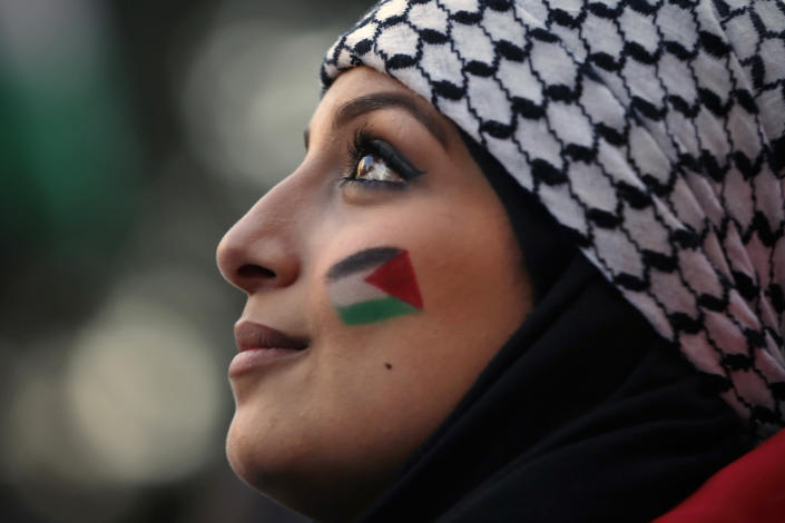 A Palestinian living in Lebanon painted Palestinian flags on her face during a march in support of Palestinians, in Beirut, Lebanon, Tuesday, May 18, 2021. (AP Photo/Bilal Hussein)