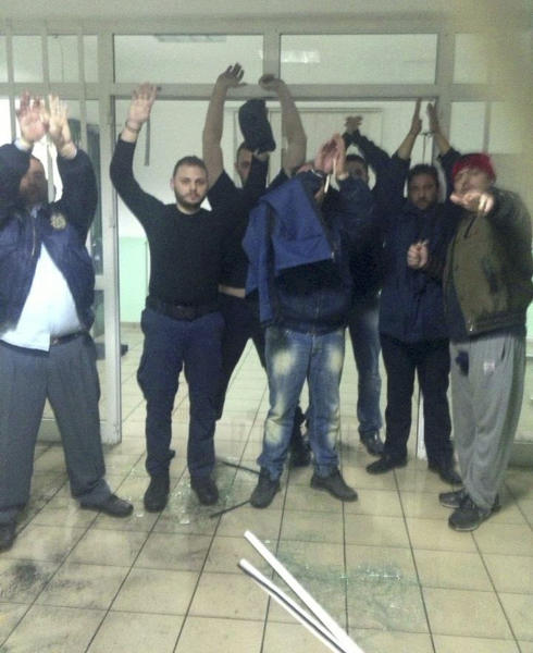 This photo taken by an unnamed prisoner with a cellphone purportedly shows Albanian convict Alket Rizaj, right, holding something in his right hand while standing with six hostages, both prison officers and prisoners, at Malandrino prison, in central Greece, on Saturday, March 16, 2013. Rizaj is demanding to be allowed to leave the prison, claiming to be heavily armed. Police special forces have deployed outside the prison, while prison officers, Rizaj's lawyer, and a prosecutor try to negotiate with him. (AP Photo)