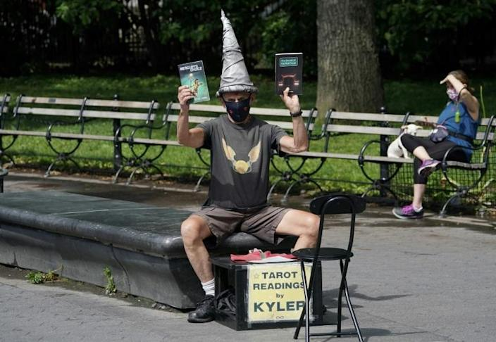 Fixture-and-tarot-card-wizard Kyler James sits in Washington Square Park in New York on June 9, 2020 (AFP Photo/TIMOTHY A. CLARY)