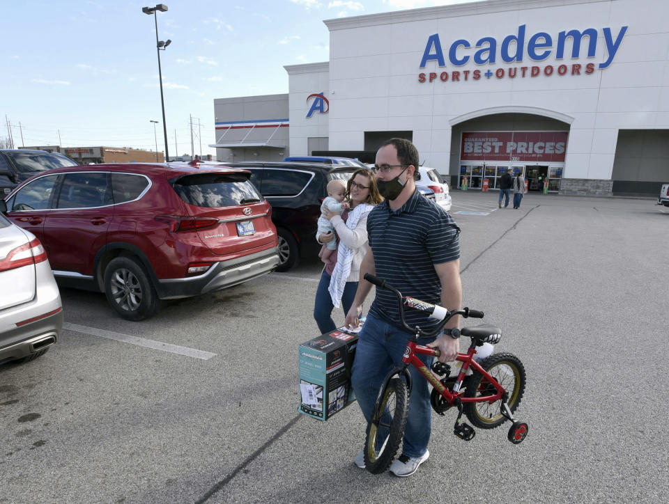 FILE - In this Friday, Nov. 27, 2020, file photo, Aaron and Jessica Elder, of Hartford, carrying Boyd, 7 months, purchased two bikes for their children for Christmas presents while shopping on Black Friday at Academy Sports + Outdoors in Owensboro, Ky. A Federal Reserve survey of business conditions around the country found that economic activity in several regions was slowing in November as coronavirus cases surged. The report, released Wednesday, Dec. 2, 2020, and known as the beige book, will be used by Fed officials when they hold their last meeting of the year on Dec. 15-16 to discuss possible changes to the central bank's interest-rate policies. (Alan Warren/The Messenger-Inquirer via AP, File)