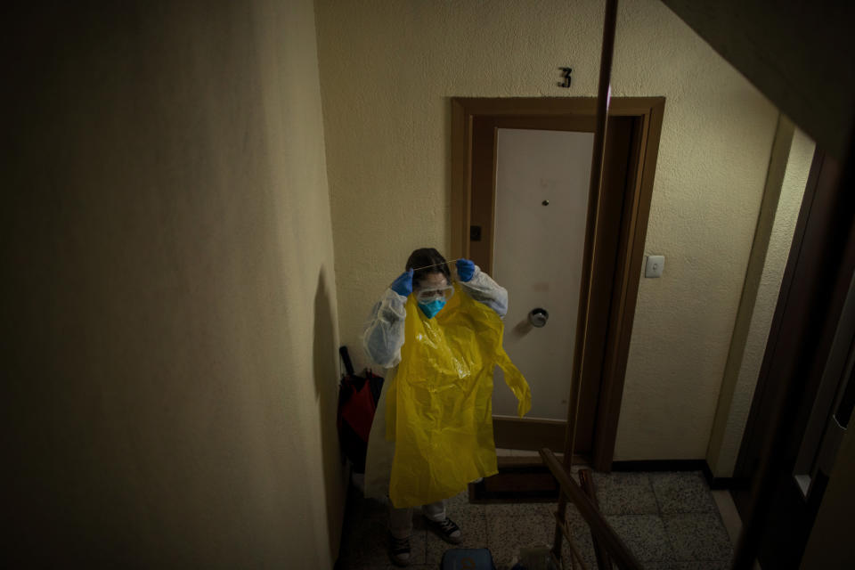 """Home care nurse Alba Rodriguez puts on protective gear before visiting a patient in the Poble Sec neighborhood of Barcelona, Spain, March 30, 2020. A pediatric nurse by profession, Rodriguez has gotten creative to try to protect herself, fashioning hazmat suits out of giant yellow garbage bags that she and fellow nurses wear over their scrubs as extra protection. """"We're like onions,"""" she says of the extra layers. (AP Photo/Emilio Morenatti)"""