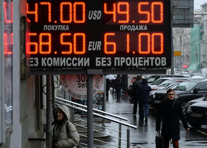 Pedestrians walk under a board listing foreign currency rates against the Russian ruble outside an exchange office in central Moscow, on November 7, 2014 (AFP Photo/Vasily Maximov)