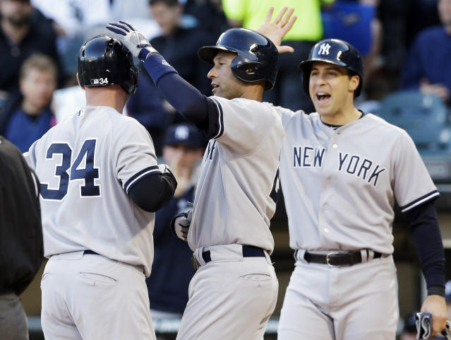 New York Yankees' Brian McCann (34) celebrates with Derek Jeter, center, and Mark Teixeira after hitting a three-run home run during the first inning of a baseball game against the Chicago White Sox in Chicago on Friday, May 23, 2014. (AP Photo/Nam Y. Huh)