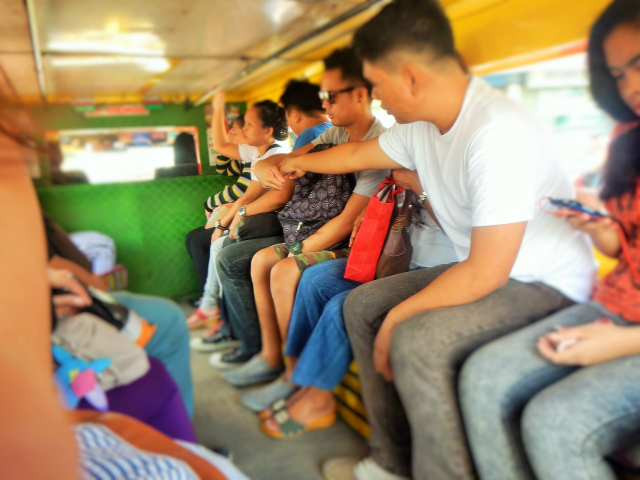 Commuters paying fare in a jeep