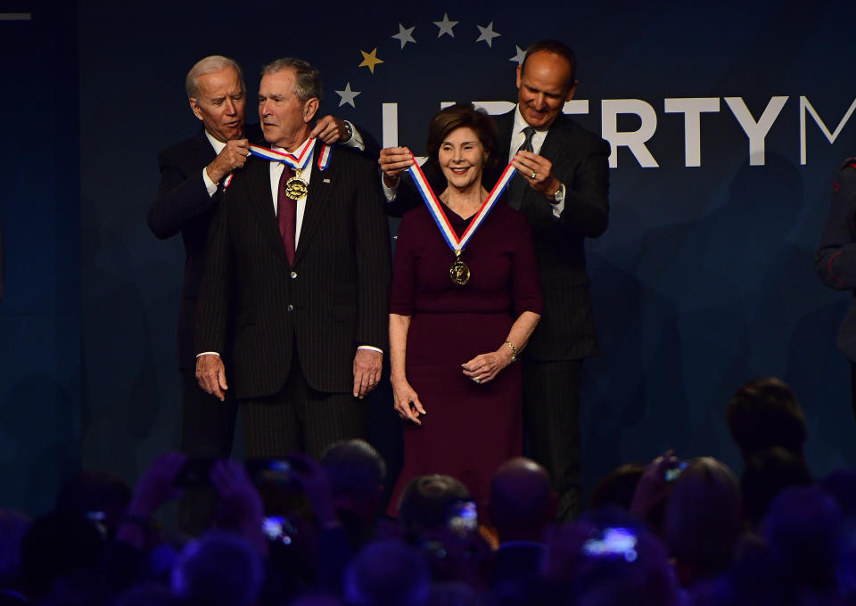 Former U.S. Vice President Joe Biden, from left, bestows a medal on former U.S. President George Bush as former first lady Laura Bush has the same bestowed by Doug DeVos, executive committee chairman for the National Constitution Center, at the National Constitution Center, Sunday, Nov. 11, 2018 in Philadelphia. Both received the 30th annual Liberty Medal, an honor given to those who are committed to freedom and human rights globally. (AP Photo/Corey Perrine)