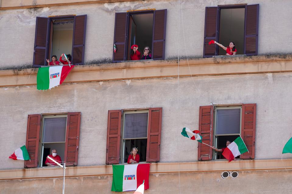 """People wave and chant from their windows with the Italian flags draped on the occasion of the 75th anniversary of Italy's Liberation Day, in Rome, Saturday, April 25, 2020. Italy's annual commemoration of its liberation from Nazi occupation is celebrated on April 25 but lockdown measures in the coronavirus-afflicted country mean no marches can be held this year and the National Association of Italian Partisans has invited all to sing """"Bella Ciao"""", the anthem of Italy's communist resistance, from their windows. (AP Photo/Andrew Medichini)"""