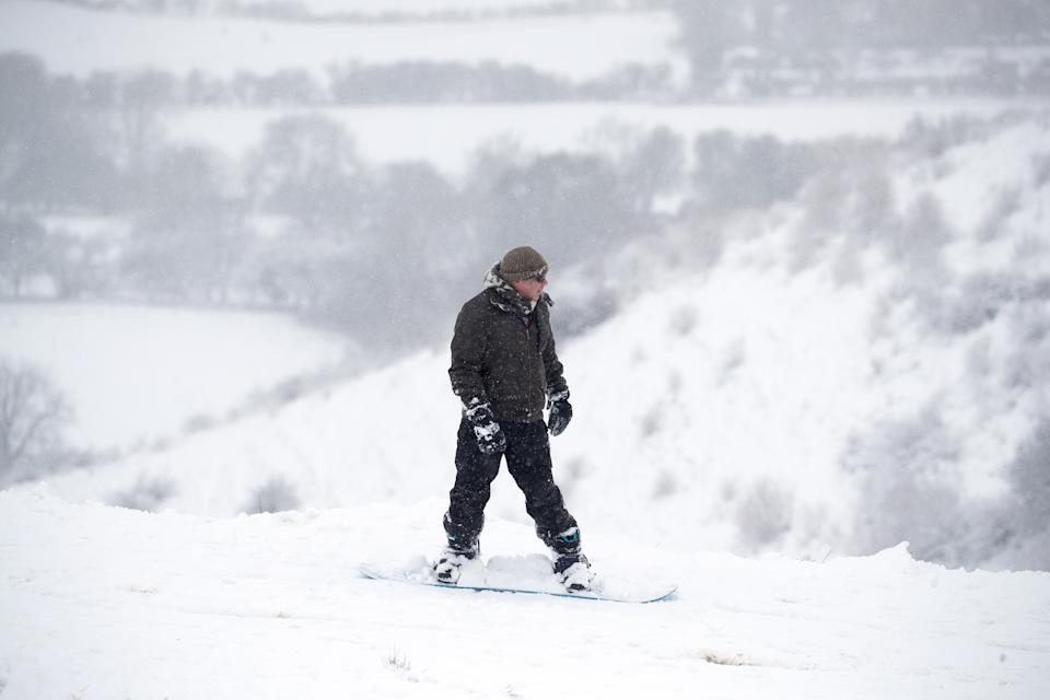 A snow boarder makes their way through the snow in Wye National Nature Reserve near Ashford in Kent, with heavy snow set to bring disruption to south-east England and East Anglia as bitterly cold winds grip much of the nation. Picture date: Sunday February 7, 2021.