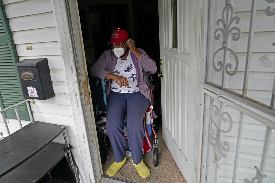 "Helen Green puts on her face mask as a box of meals is delivered by Revolution Foods in New Orleans on Thursday, Feb. 11, 2021. Green, 76, must use a walker to get around and depended on her 96-year-old mother to cook for both of them before the older woman fell and went to an assisted living facility. ""I'm very thankful for these meals. It makes a big difference in your life, you know,"" she said. (AP Photo/Gerald Herbert)"