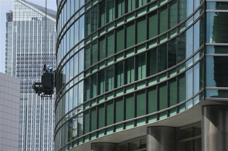 Workers stand in a cleaning gondola as they wipe the windows of a building in Tokyo's business district