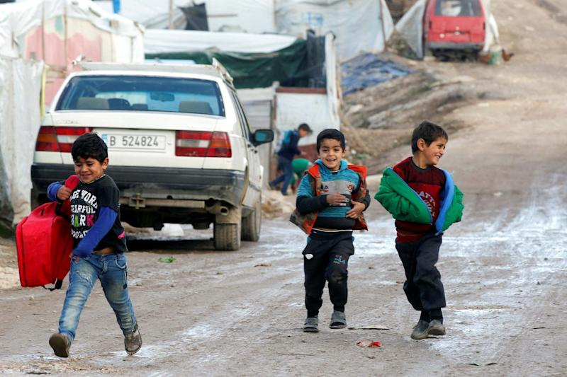 Syrian refugee boys walk together at a camp in Lebanon (REUTERS)