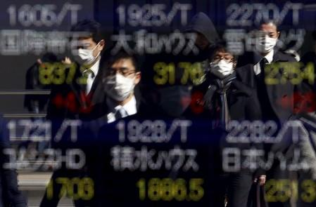 Pedestrians wearing masks are reflected in an electronic board showing various stock prices outside a brokerage in Tokyo, Japan