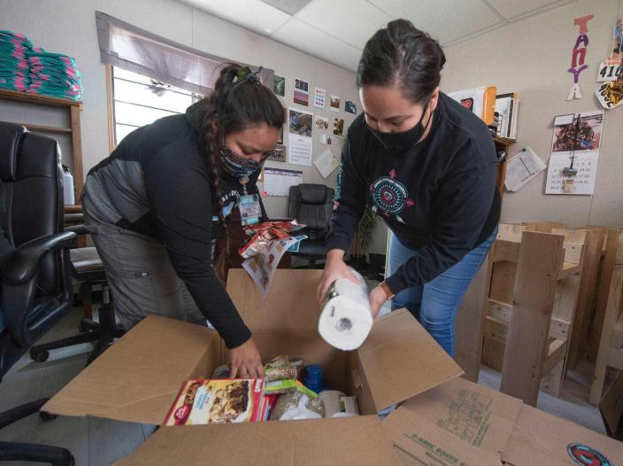 "<span class=""caption"">At the Navajo Nation town of Fort Defiance, Arizona, staff pack food boxes. The Navajo Nation now has the highest per capita COVID-19 infection rate in the U.S. </span> <span class=""attribution""><a class=""link rapid-noclick-resp"" href=""https://www.gettyimages.com/detail/news-photo/staff-from-the-john-hopkins-center-for-american-indian-news-photo/1214296194?adppopup=true"" rel=""nofollow noopener"" target=""_blank"" data-ylk=""slk:Getty Images / Mark Ralston"">Getty Images / Mark Ralston</a></span>"