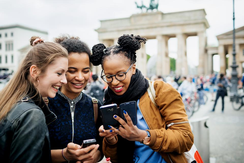 A group of friends travelling together are exploring the local tourist attractions and architecture, they stop for a moment to look over recent photos on their phones.