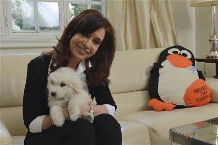 Argentine President Fernandez poses with her dog at the Olivos Presidential residence in Buenos Aires