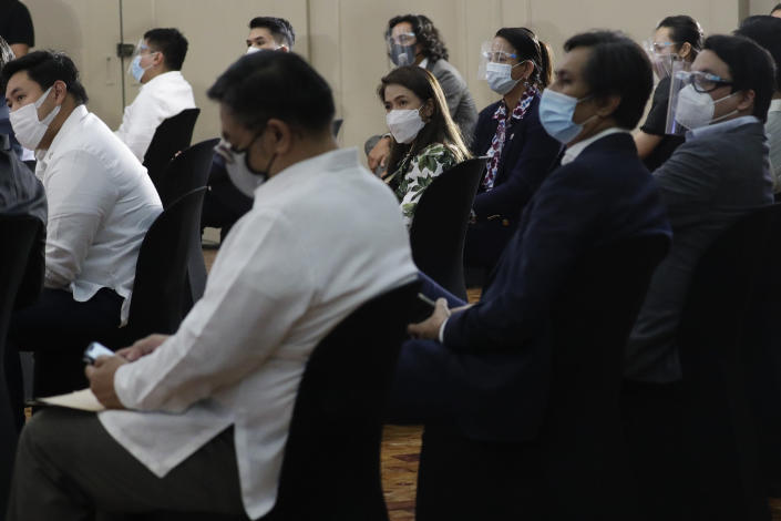 """Filipino lawmakers wear face masks as they attend a session before swearing in Rep. Lord Allan Velasco as new house speaker at the Celebrity sports club in Quezon city, Philippines, Monday, Oct. 12, 2020. A large faction of Philippine legislators in the House of Representatives has elected a new leader but the incumbent speaker declared the vote """"a travesty"""" in a tense political standoff between two allies of the president. (AP Photo/Aaron Favila)"""