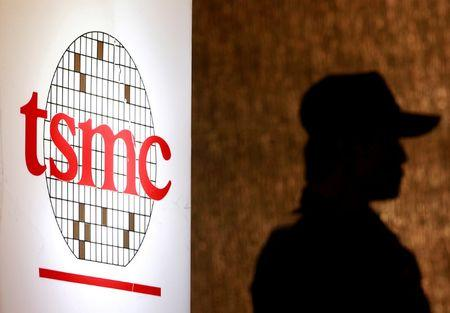 FILE PHOTO -  A security personnel stands near the logo of Taiwan Semiconductor Manufacturing Co. Ltd in Taipei
