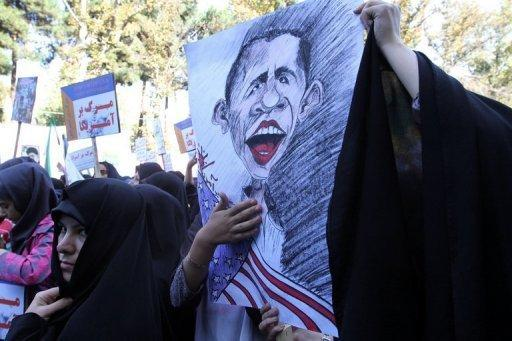 A Iranian woman holds a cartoon image of Barack Obama during an anti-US rally in Tehran on November 2