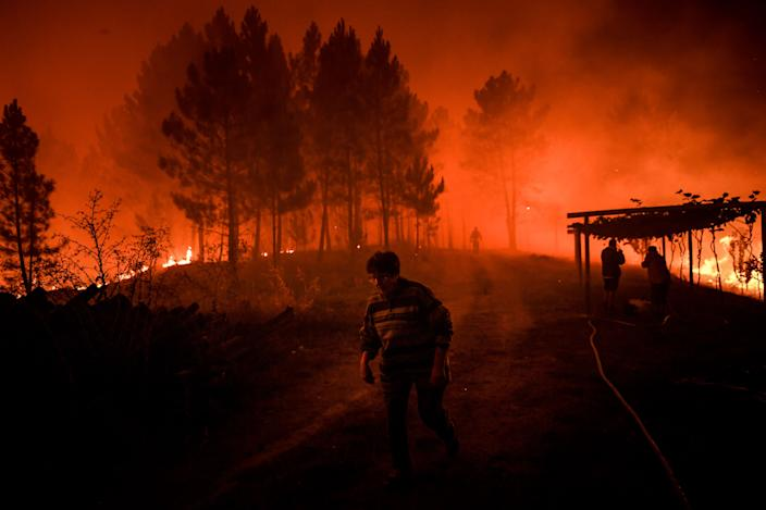 A villager walks past a wildfire encroaching on her home in Amendoa in Macao, central Portugal on July 21, 2019. (Photo: Patricia De Melo Moreira/AFP/Getty Images)