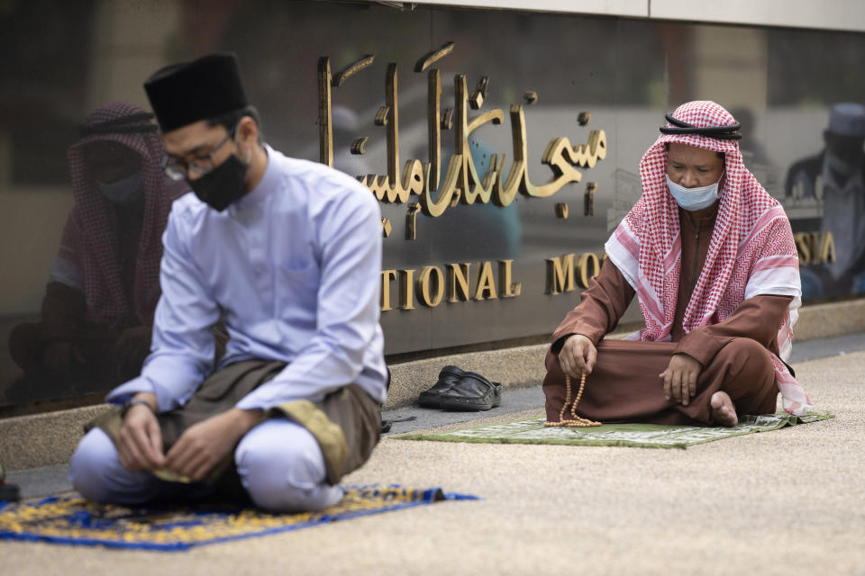Muslims wearing protective masks prepare to pray outside the closed National Mosque while celebrating Eid al-Fitr, the Muslim festival marking the end the holy fasting month of Ramadan, amid the coronavirus outbreak, in Kuala Lumpur, Malaysia, Sunday, May 24, 2020. (AP Photo/Vincent Thian)