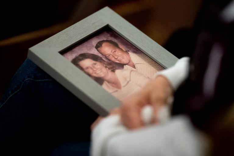 During a church vigil in Chico, California, for victims of the Camp Fire, Laura Martin holds a picture of TK Huff, her father who died in the blaze