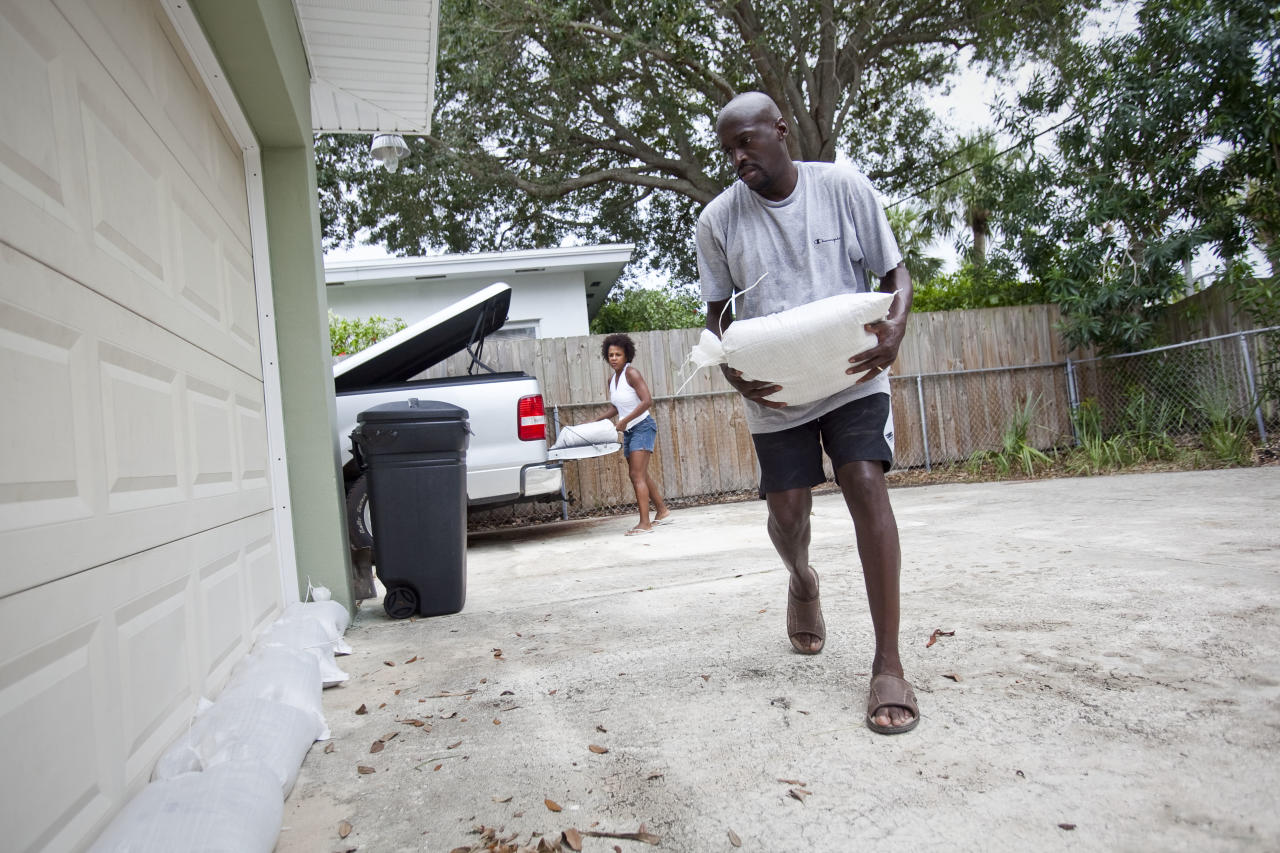 ST. PETE BEACH, FL - AUGUST 26:  Earl (R) and Terri Harris prepare their home for possible flood water ahead of Tropical Storm Isaac August 26, 2012 in St. Pete Beach, Florida. According to reports, Isaac has become stronger as it moves toward the Florida Keys and forecasters say it could strengthen into a Category 2 storm. (Photo by Edward Linsmier/Getty Images)